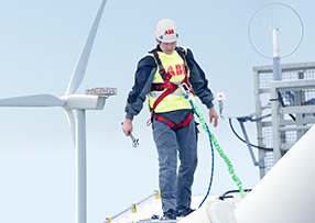 Offshore wind farm, engineer working on a gigantic wind turbine (photo)