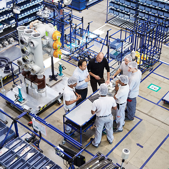 ABB employees standing in a production plant and discussing (photo)