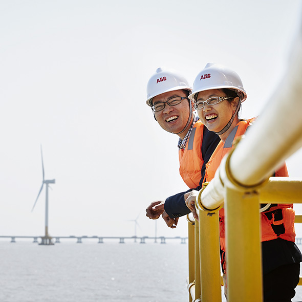 ABB engineers with offshore wind park in background (photo)